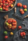 Fresh colorful ripe Fall heirloom tomatoes in basket, herb chopper knife