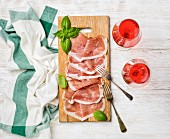 Prosciutto di Parma ham slices and fresh basil leaves on wooden board