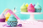 Türkisfarbener Geburtstags-Cupcake mit Wunderkerze