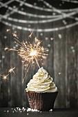 Cupcake mit Wunderkerze vor Holzhintergrund