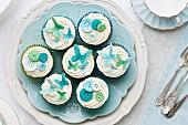 Cupcakes mit Zucker- Schmetterlingen und Knöpfen verziert