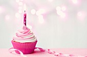 Pink birthday cupcake with copy space to side