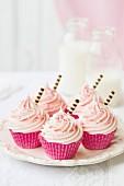 Rosa Cupcakes mit Schokoröllchen dekoriert