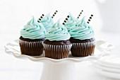 Schokoladen-Cupcakes mit Schokoröllchen dekoriert