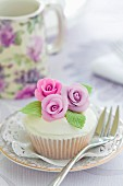 Cupcake decorated with purple sugar roses