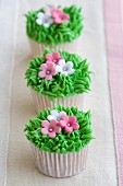 Mini cupcakes decorated with frosted grass and pink flowers