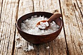 Coarse sea salt in a wooden bowl with a spoon