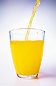 Orange Juice Pouring into a Stem Glass