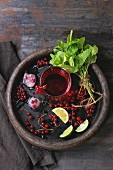 Ingredients for making lemonade: Ice cubes, red currant berries, lime, lemon and mint, served with glass of juice