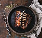 Gegrilltes Lammkarree, serviert mit Gewürzen auf Tontablett