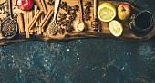 Ingredients for making mulled wine, wine in glass bottle, honey, lemon, apples and spices on wooden board