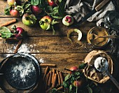 Ingredients for cooking apple pie, fresh harvest apples with leaves, cinnamon, flour, sugar and baking mold