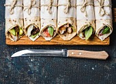Tortilla wraps with various fillings on rustic wooden board and knife over dark blue painted plywood background