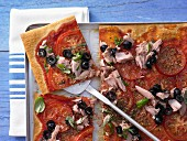 A tomato and tuna pizza with black olives and basil