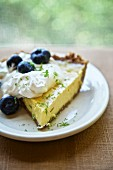 A slice of pumpkin pie with whipped cream and bluberries