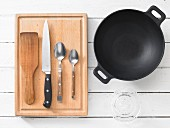 Assorted kitchen utensils: a wok, turner, knife and cutlery