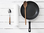 Kitchen utensils: a spoon, kitchen roll and a frying pan