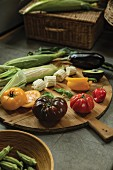 Fresh garden vegetables and corn cob on a wooden platter