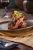 Gegrilltes Lachsfilet mit Chilis und Paprika auf Metallteller