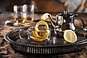 Hot toddy in a glass with lemon and a silver teapot