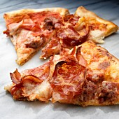 Slices of pizza with sausage, coppa and Prosciutto