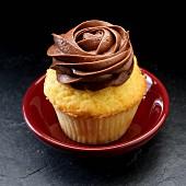 A cupcake with dark chocolate icing