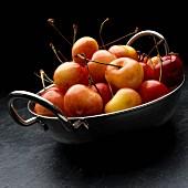Pale red Rainier cherries in a metal bowl