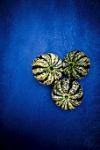 Three green and white pumpkins on a blue surface (seen from above)