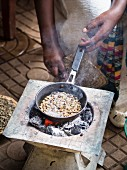 A woman roasting green coffee beans during a traditional coffee ceremony in Ethiopia