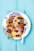 Goats' cheese and blueberry pancakes dusted in icing sugar (seen from above)