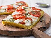 Polenta pizza with pesto, tomato and mozzarella