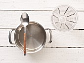 Kitchen utensils: a saucepan, spoon and measuring cup