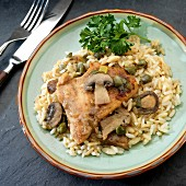 Chicken breast with mushrooms and capers on a bed of rice