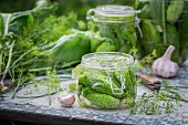 Pickled gherkins in glass jars on a garden table