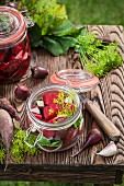 Preserved beetroot in a glass jar on a wooden crate in the garden