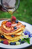 Ahornsirup auf gestapelte Pancakes mit frischen Beeren gießen
