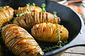 Hasselback potatoes in a frying pan