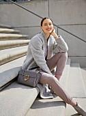 Brünette Frau grauem Wollmantel, fliederfarbenem Pullover, Lederhose und grauen Stiefeletten