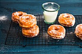 Doughnuts and a glass of milk on a cooling rack