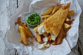 Fish and chips with mushy peas on paper