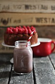 A chocolate milkshake with a straw in a glass jar with raspberry cake in the background