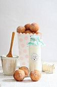 Milk in a decorative glass bottle and quark doughballs with cinnamon sugar