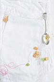 A spoon, biscuit crumbs, and kitchen string on a white tablecloth with a lace border