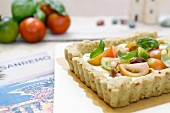 Salty tart with cream cheese, pesto, olives, pine nuts and fresh tomatoes (Liguria, Italy)