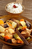 Fleisch mit gekochtem Gemüse in Holzschale (Afrika)