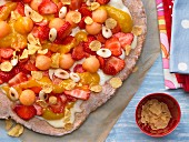 A sweet pizza with fruit, cornflakes and almonds