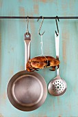 A crab hanging from a hook between a saucepan and a draining spoon