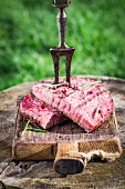 Steak with rosemary and pepper on a wooden board