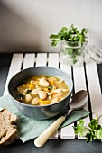 Chicken soup with butterbeans, bread and fresh parsley