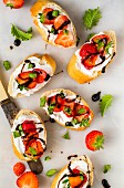 Slices of baguette with strawberries, basil, balsamic vinegar and goats' cheese